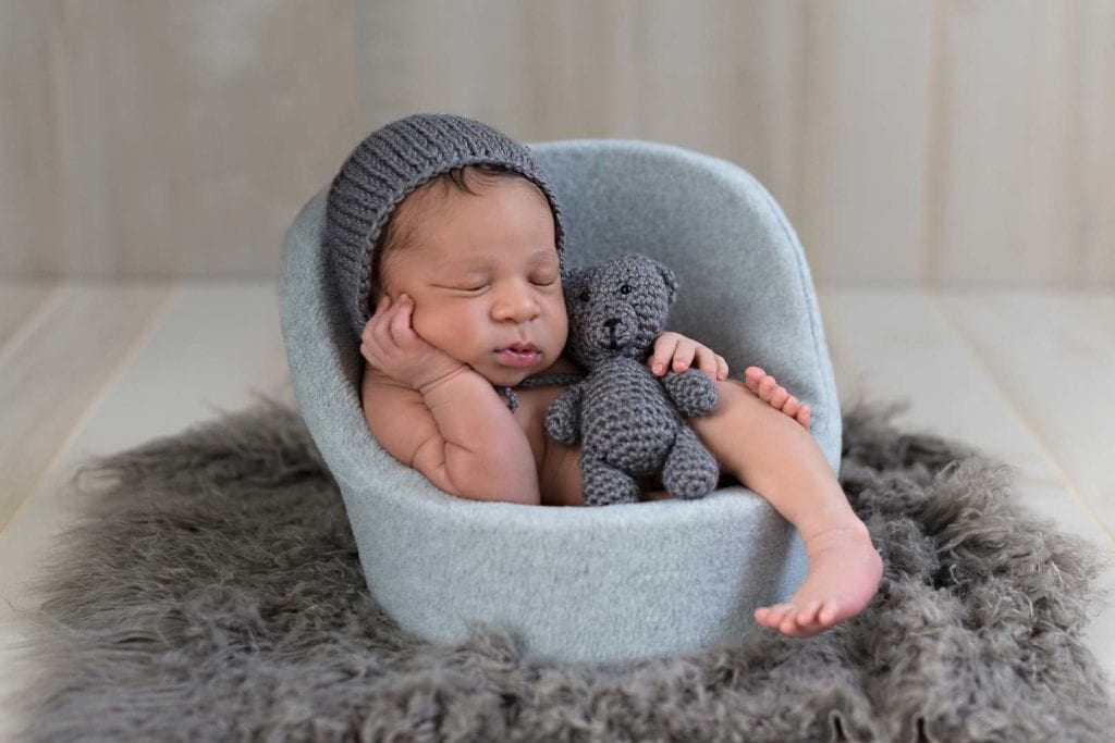 baby sleeping with gray knitted head cover and teddy bear