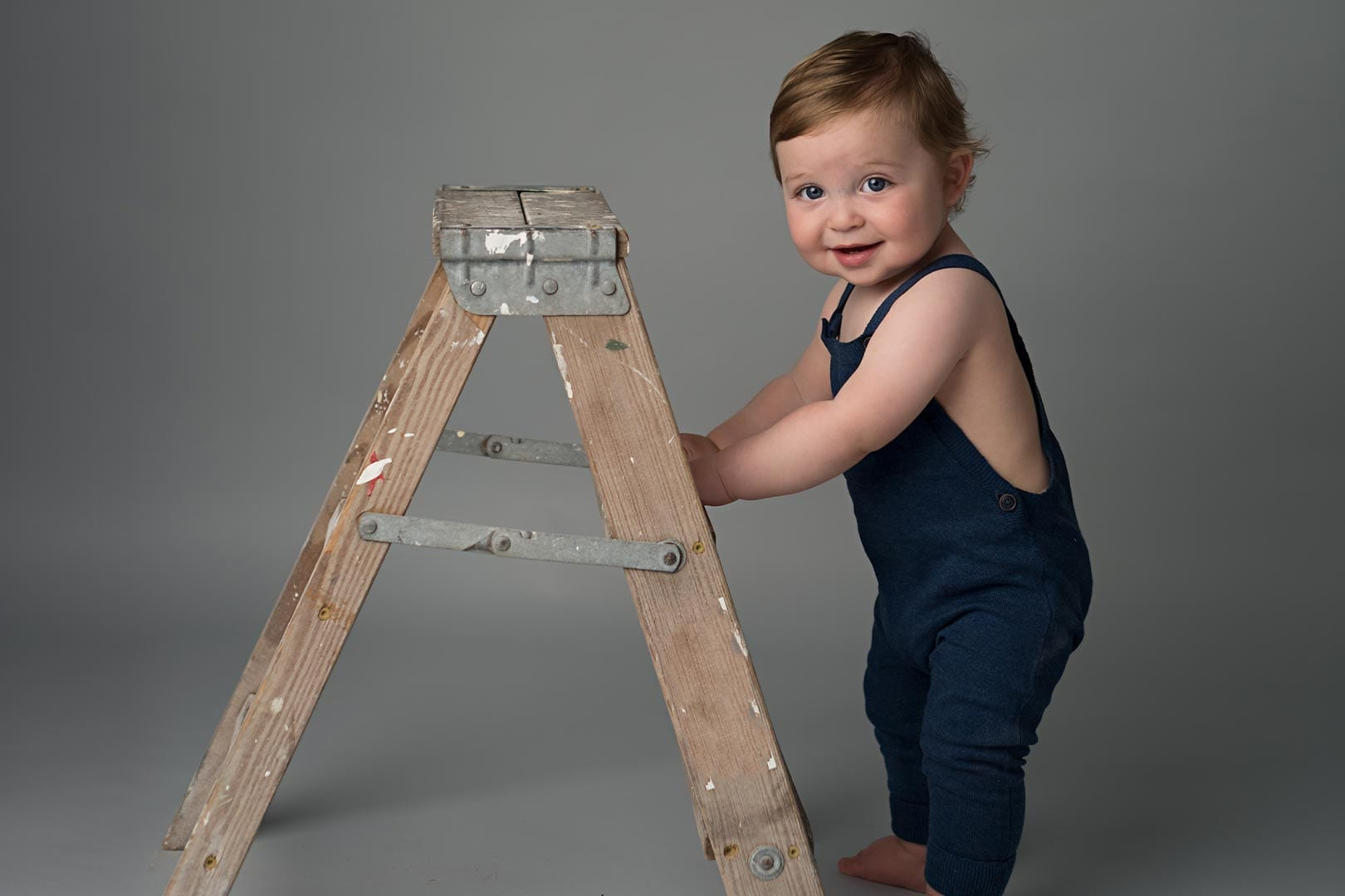 little boy wearing a blue jumper holding the ladder