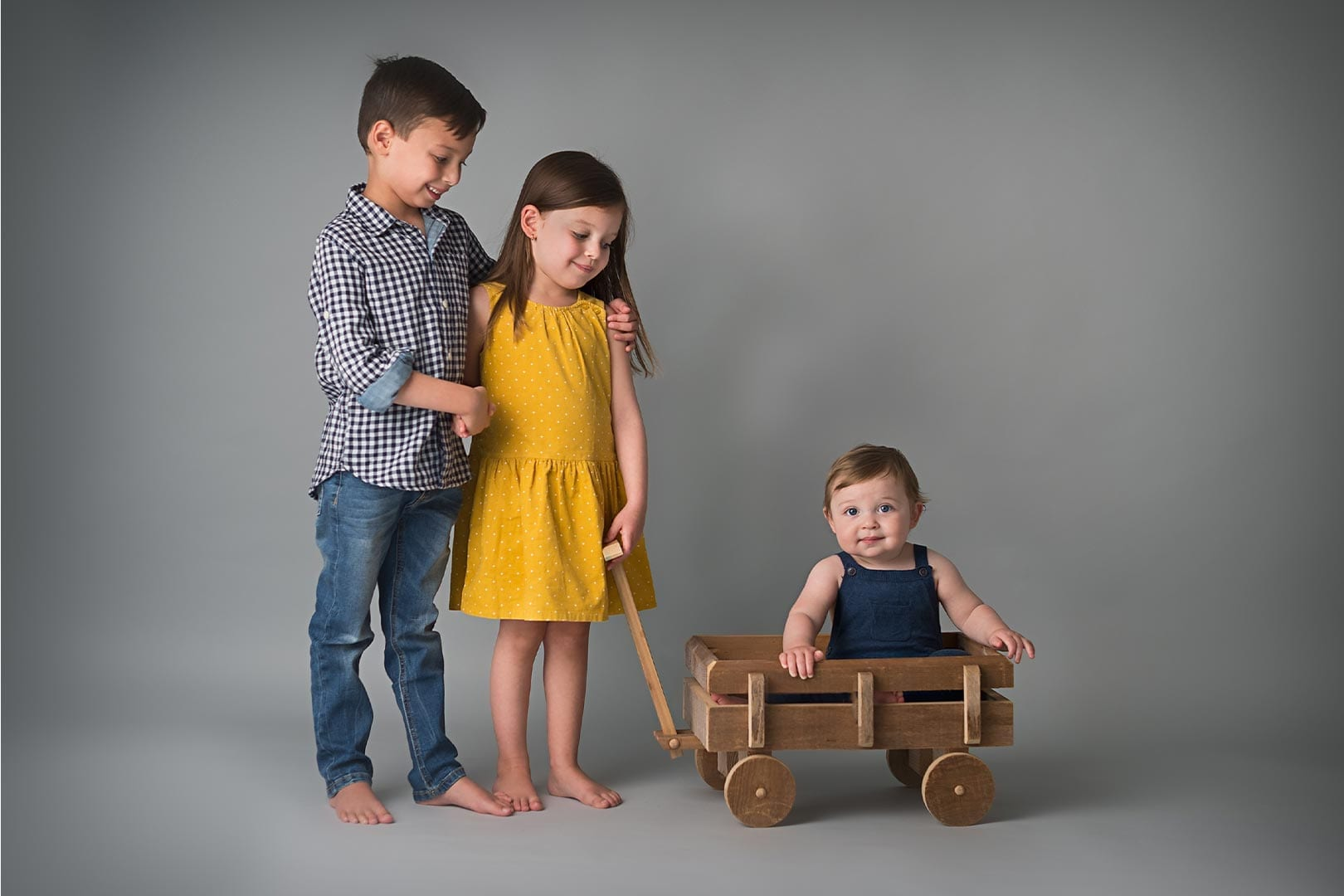 a toddler in the wooden cart with her siblings