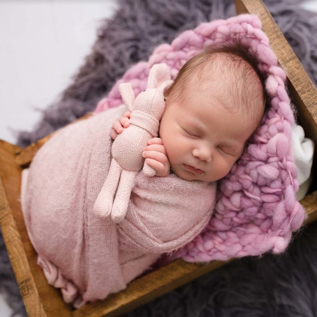 sleeping baby cover in pink cloth lying in wooden bed